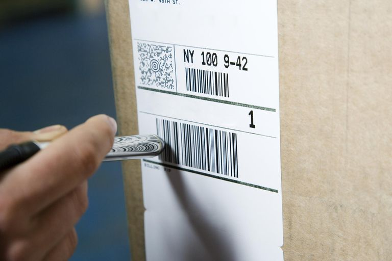 Warehouse worker using electronic barcode reader, close-up of hand