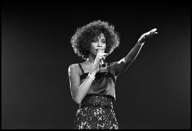 Whitney Houston singing with arm outstretched.