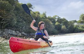 A woman paddles in a sea kayak