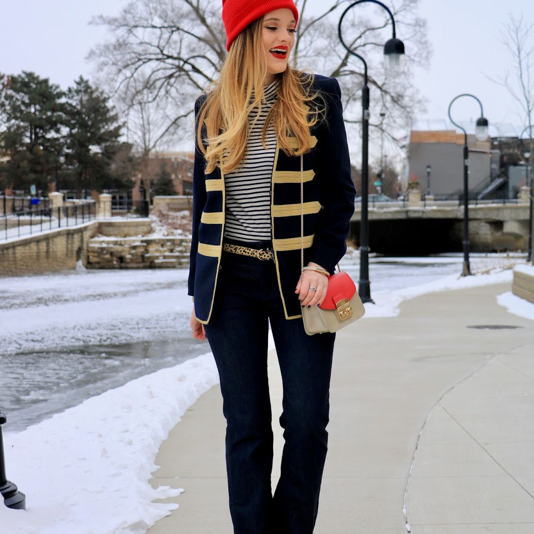 Woman in military style jaket and jeans and red hat for fall and winter style