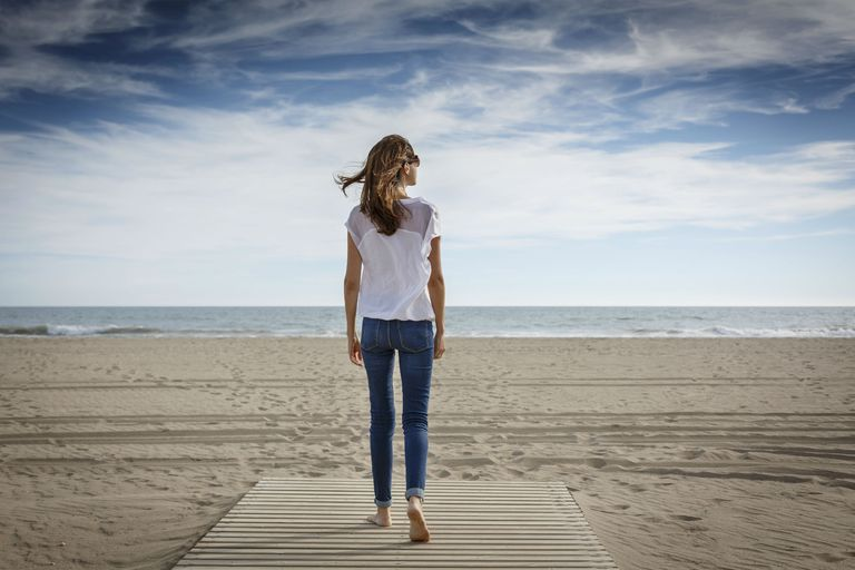 Woman in jeans walking on the beach