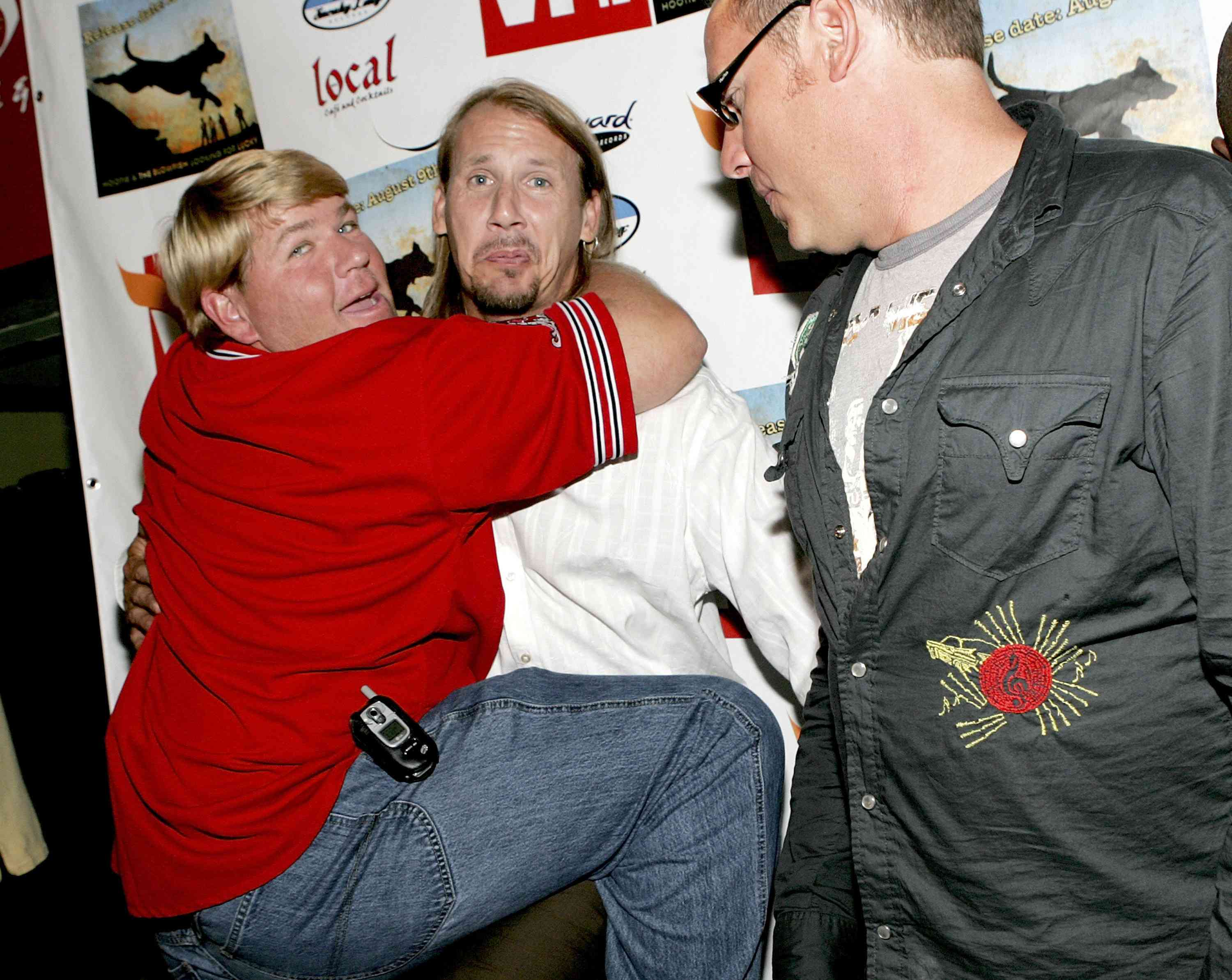 """Golfer John Daly jokes with Hootie and the Blowfish band members Jim """"Soni"""" Sonefeld (C) and Dean Felber (R) as they attend a listening party for their new CD """"Looking for Lucky"""" at Local 1 August 8, 2005"""