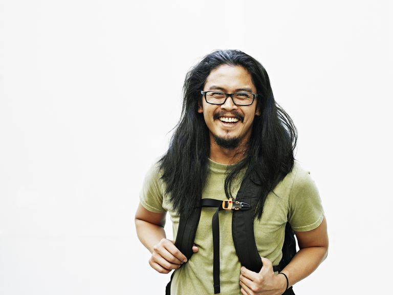 Asian man with long hair wearing a backpack and green shirt