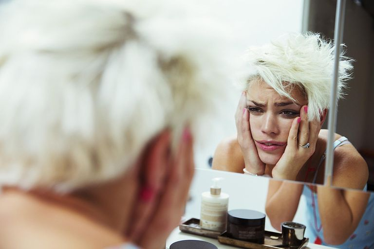 Hungover woman examining her face in mirror.
