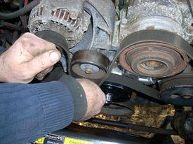 inspecting a serpentine belt on car