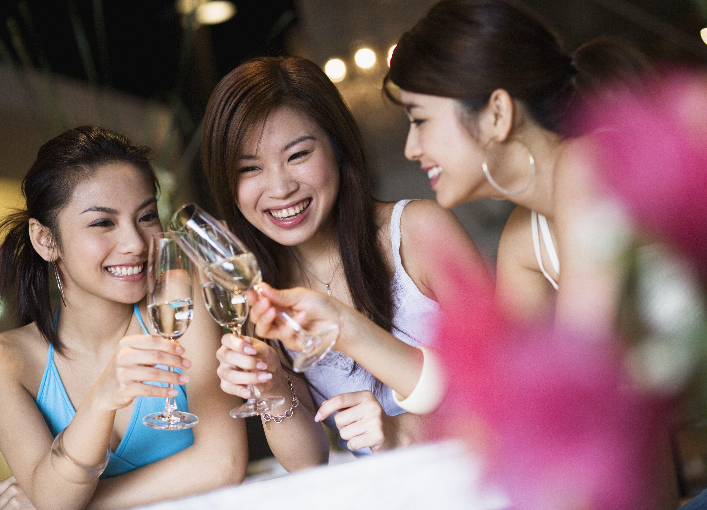 Three Young Women Toasting at Bar