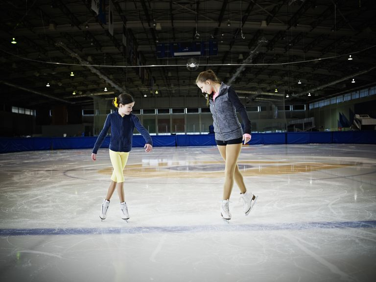 Figure skater teaching young student on ice