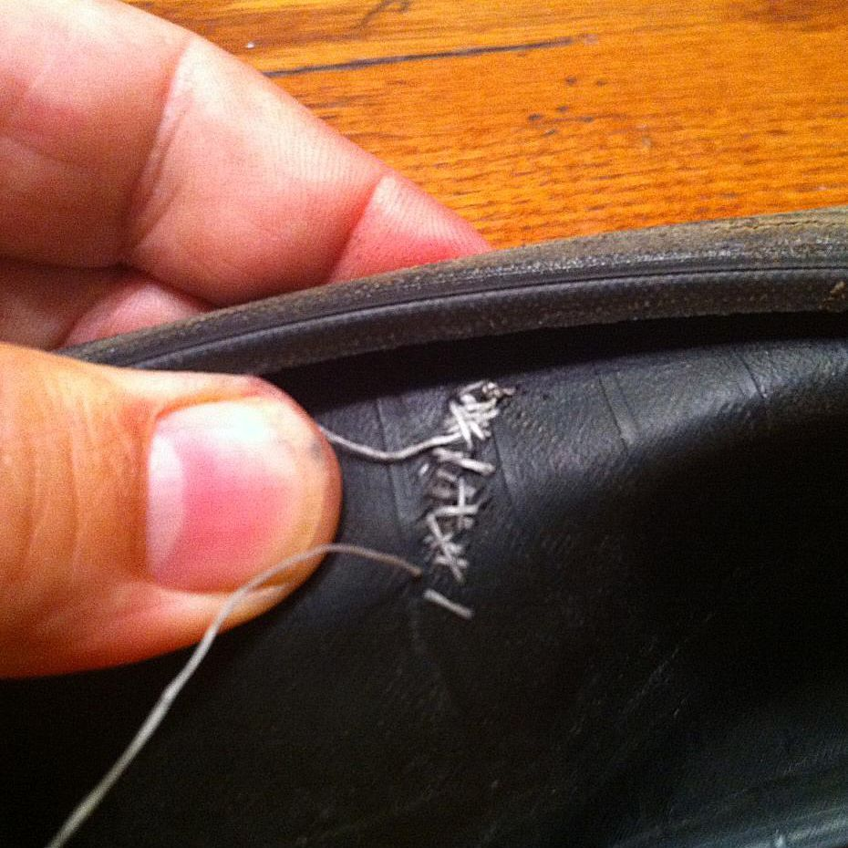 Using a needle and dental floss to repair a gash in a bike tire sidewall