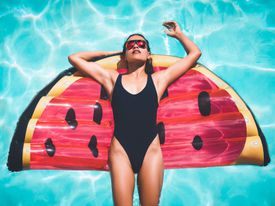 Woman in black swimsuit floating in a pool on a watermelon inflatable