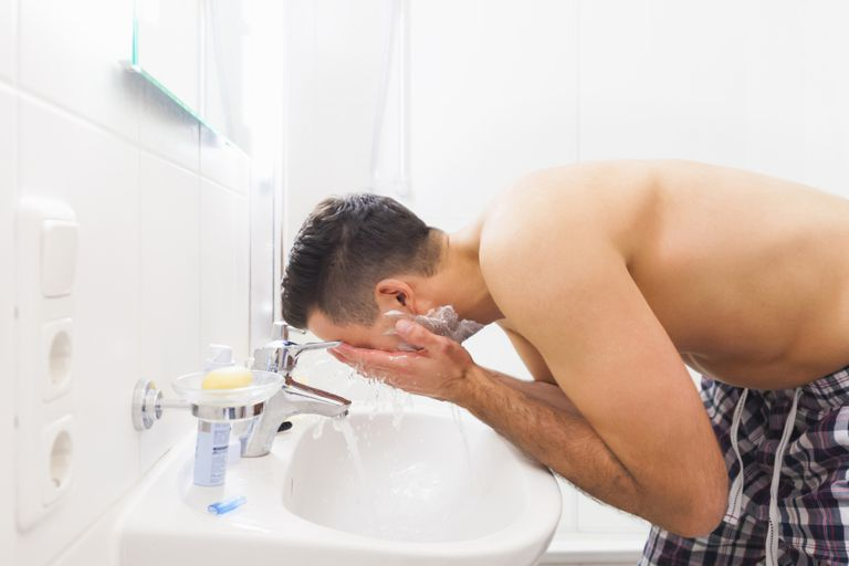 Young man washing face in bathroom sink