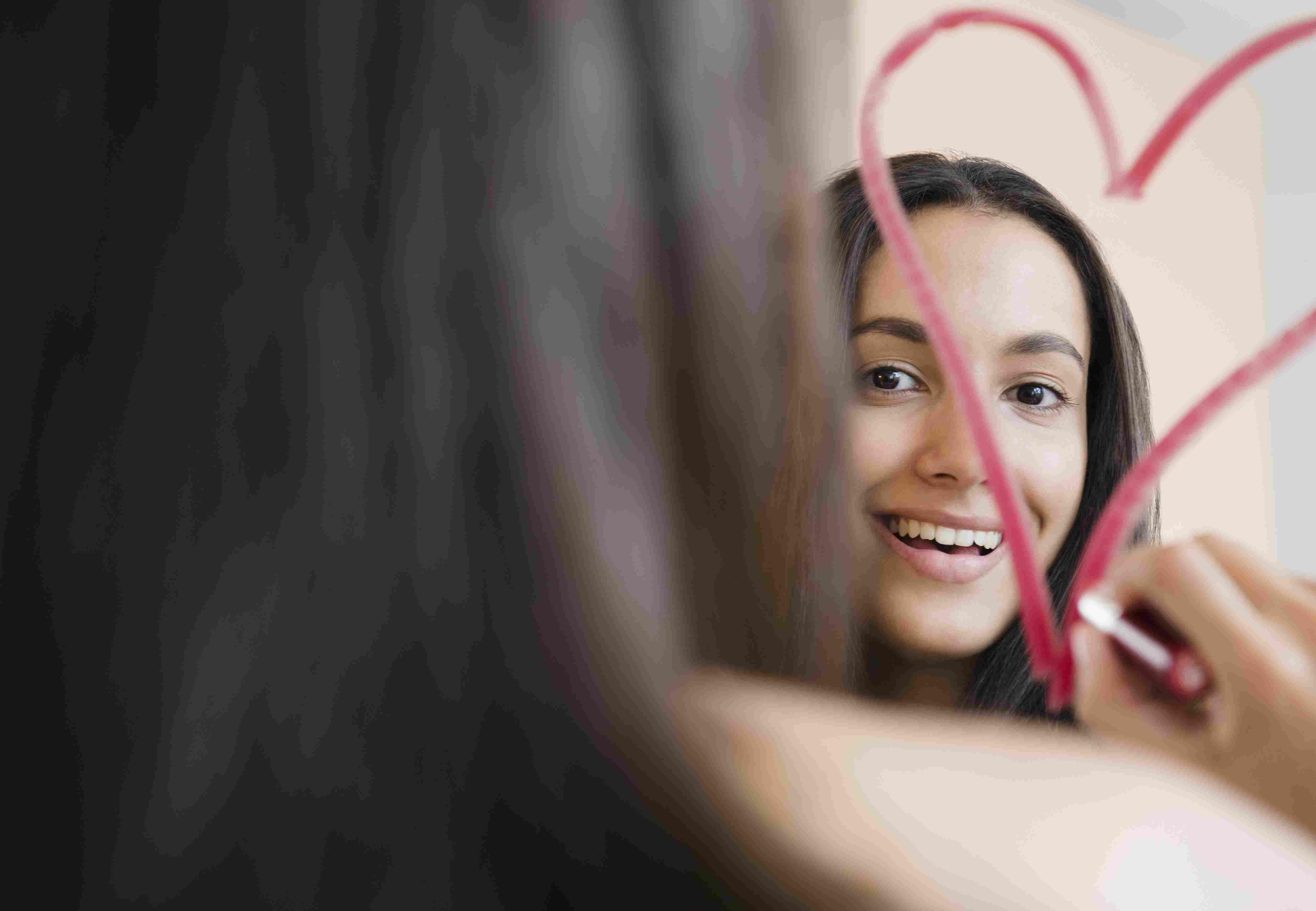 Hispanic teenager drawing heart with lipstick