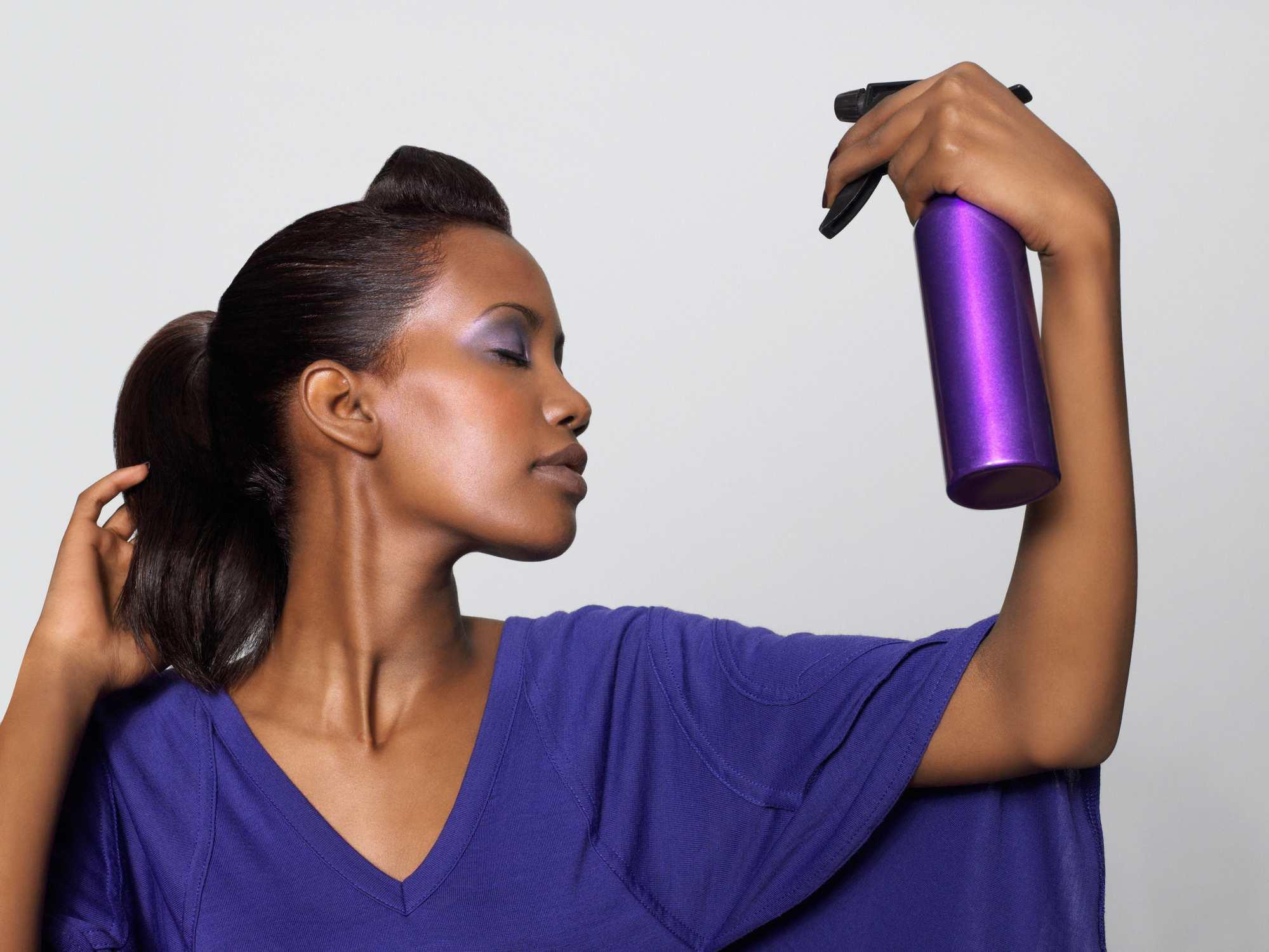 black woman spraying hair with natural hair spritz