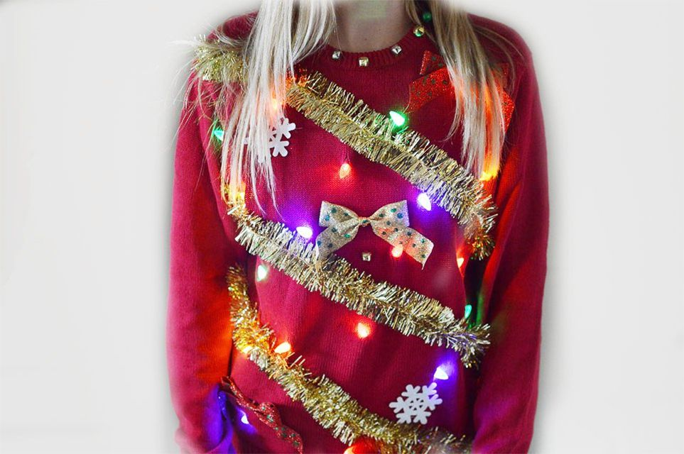 A woman wearing an ugly Christmas sweater with lights
