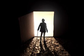 Someone stands in ominously in an open doorway in the dark