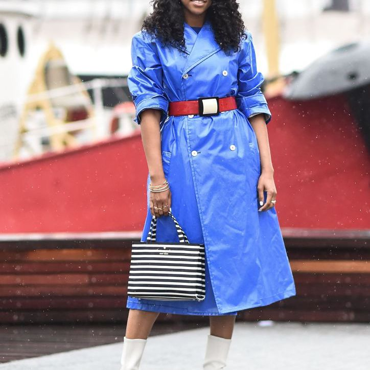 Woman in bright blue raincoat and striped purse and white boots