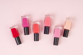 Row of six small bottles of nail polish in various shades of pink, overhead view