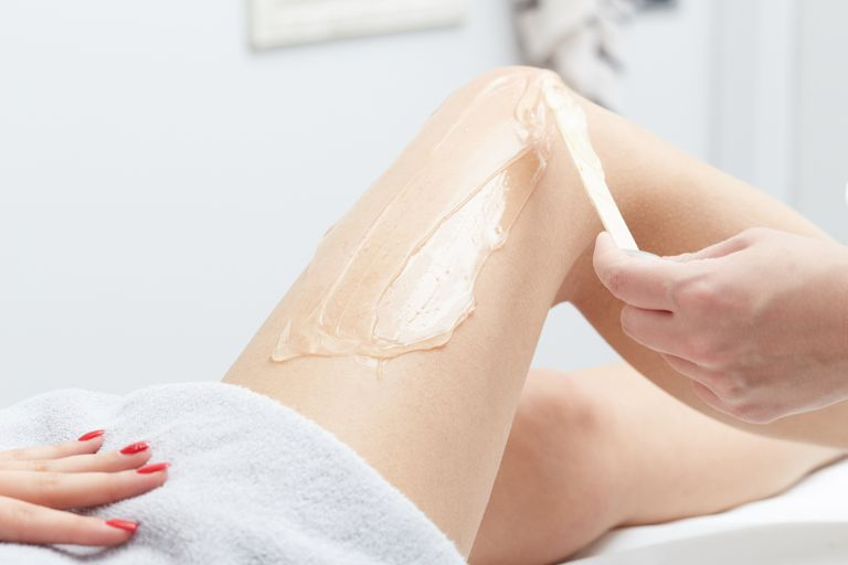 Wax being smoothed over a woman's leg