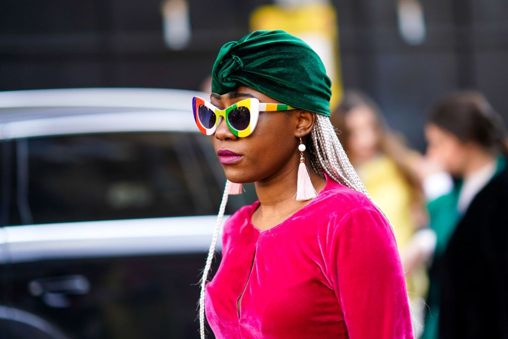 Street style woman wearing green turban plastic sunglasses and tassel earrings