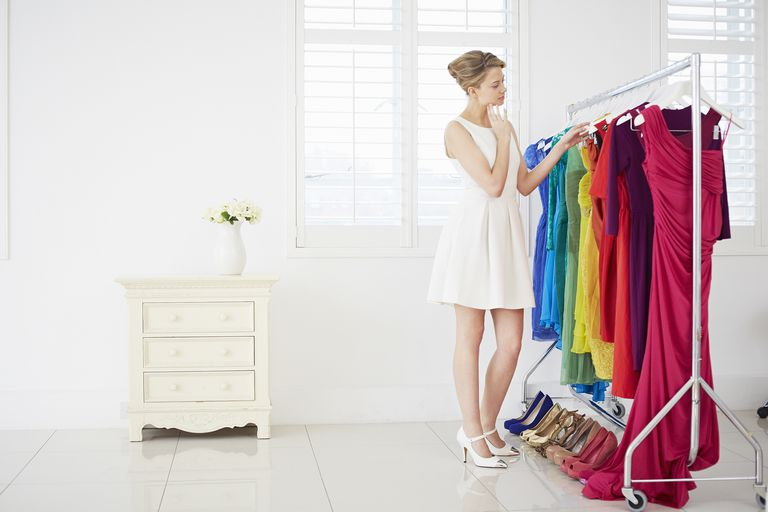 Woman selecting outfit from colorful wardrobe of dresses and shoes.
