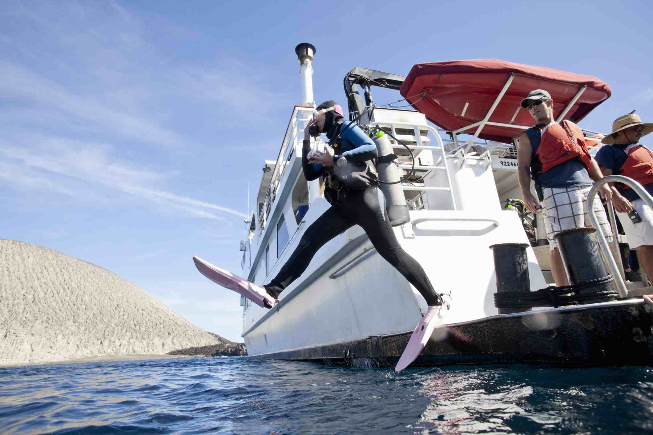 A scuba diver holding a camera in underwater housing jumps off the deck of a live aboard boat