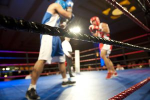 Boxers Fighting in a Ring With Referee