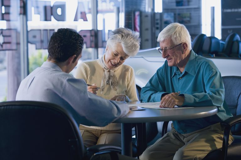 Senior couple signing papers in car dealership
