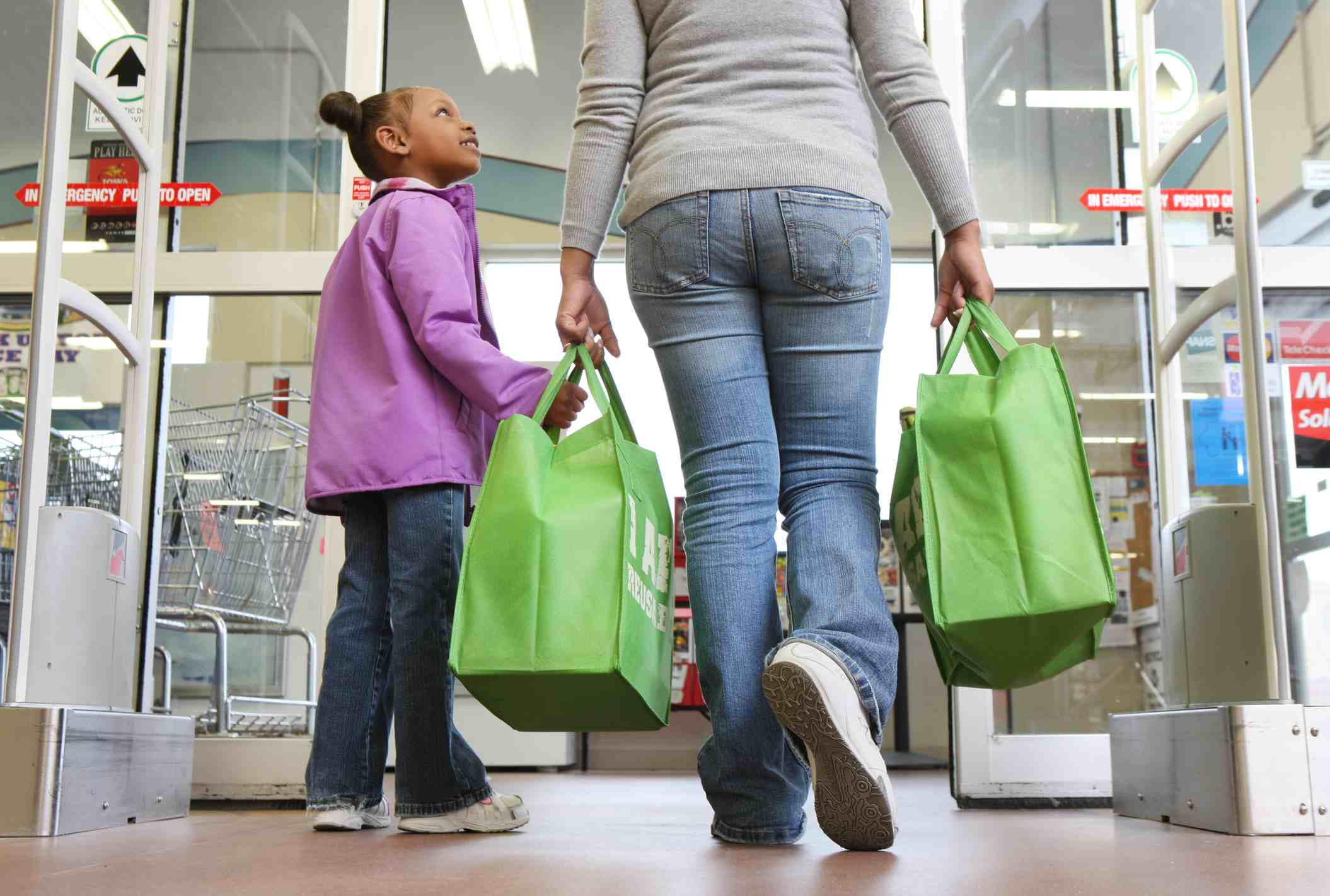 Mom and daughter walking out of store carrying reusable grocery bags