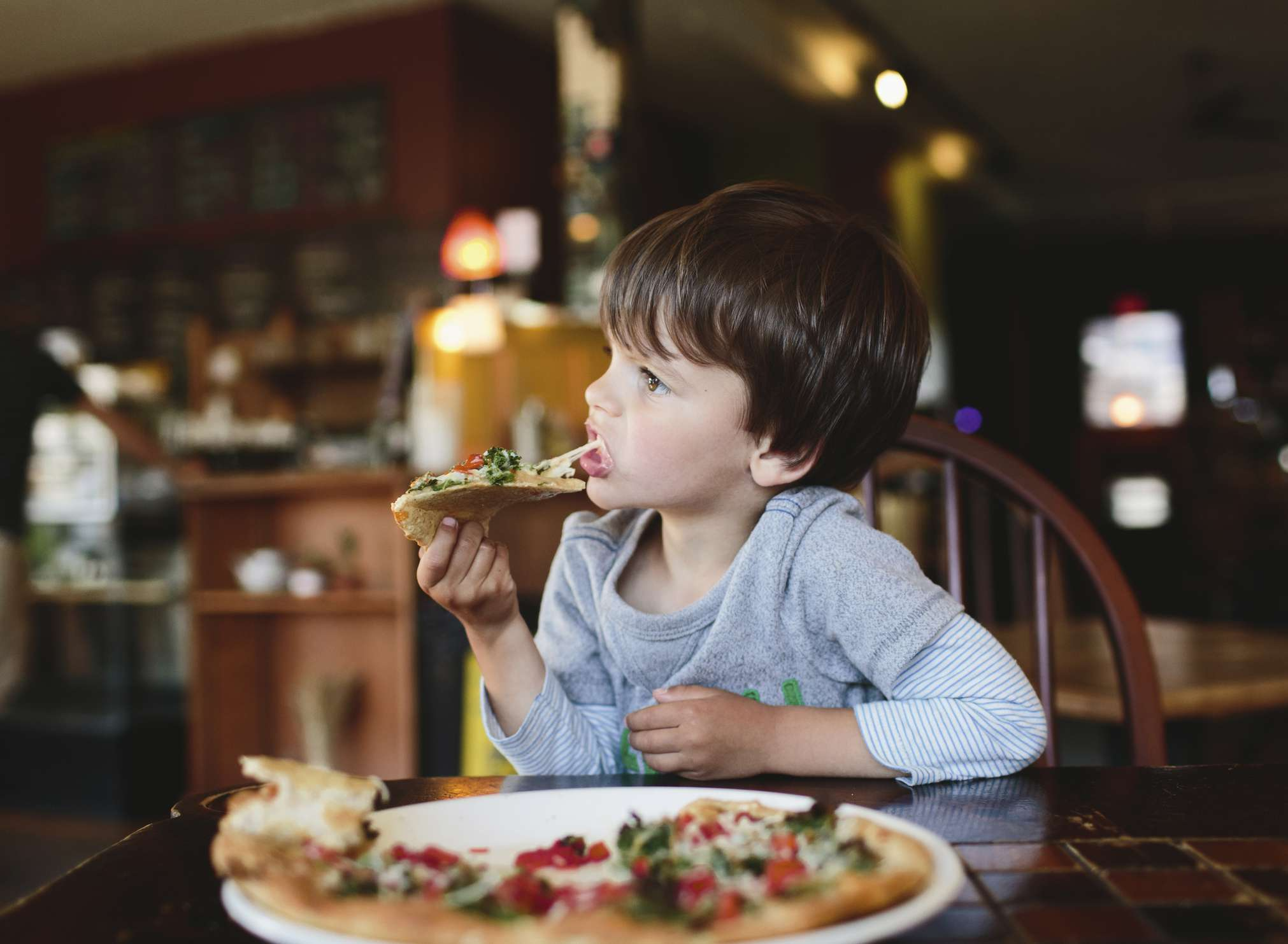Boy Eating Pizza in Restaurant