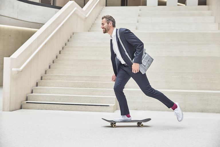 Businesssman riding skateboard at staircase