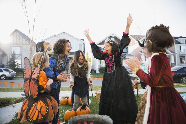 Exuberant Girl in Halloween Costume Bobbing for Apples