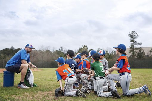 Coach talking to youth baseball team on field