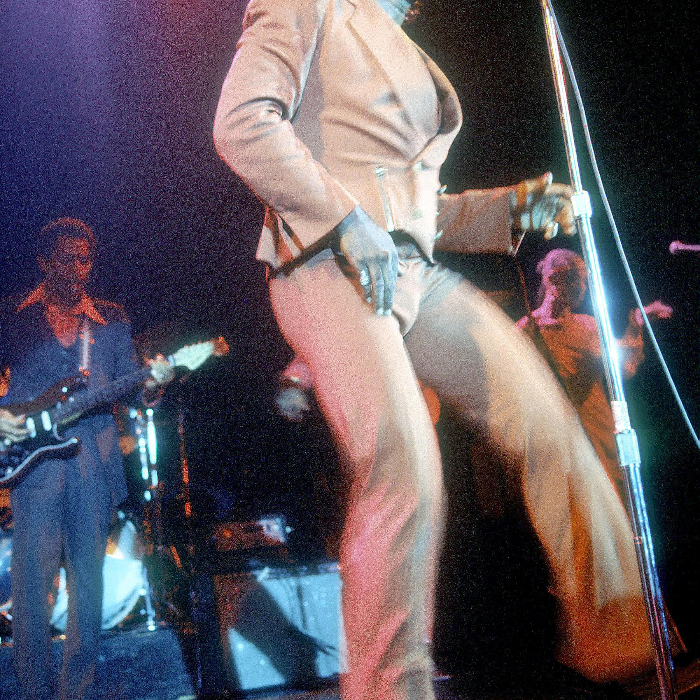 James Brown singing and dancing on stage.