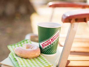 A Krispy Kreme glazed doughnut and a cup of coffee.