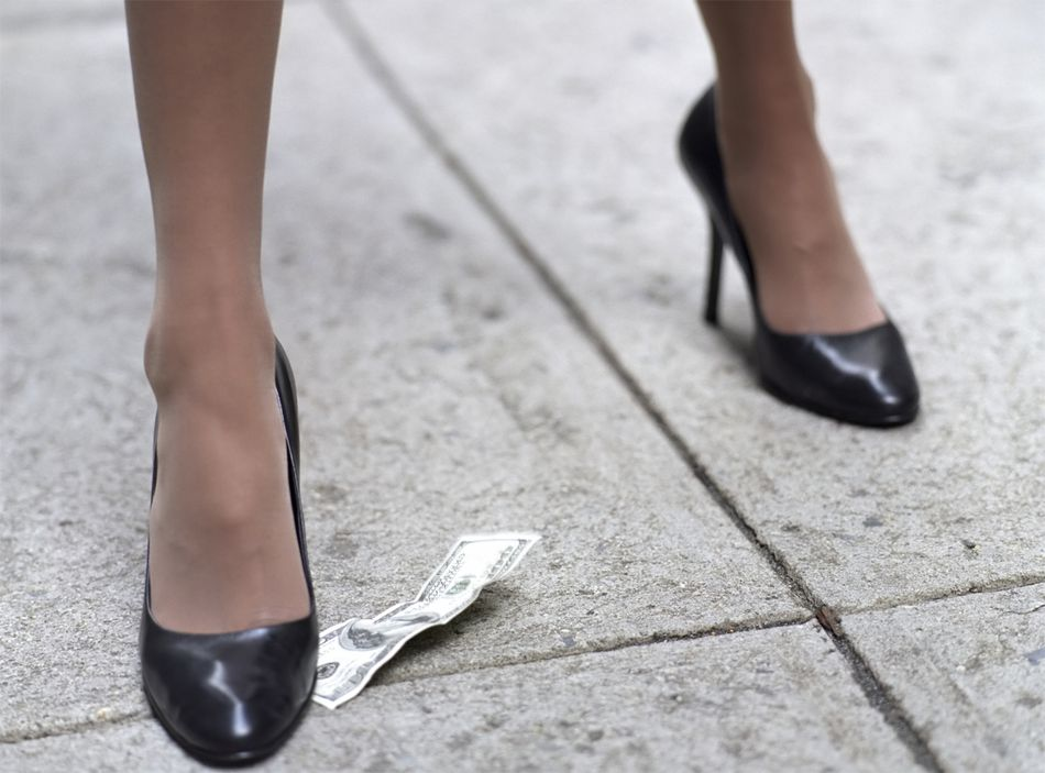 Women stepping on money on the street.