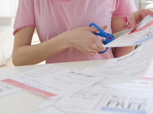 woman cutting out coupons