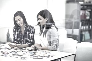 Women reviewing pictures in office meeting