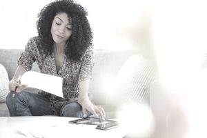 Mixed race woman paying bills on digital tablet