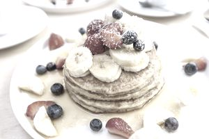 Close-up of delicious pancakes with fresh fruits, berries and maple syrup on a plate