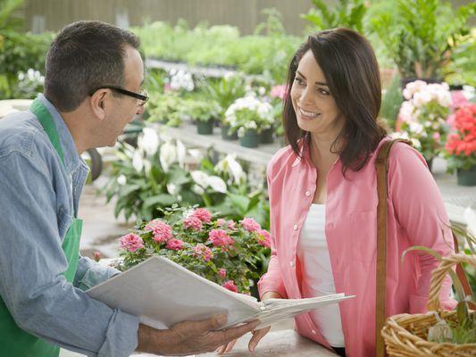 Florist showing customer binder of inventory