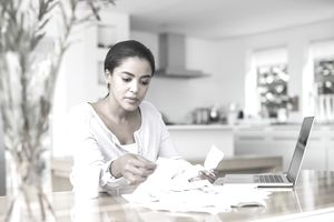 A woman paying bills online at home