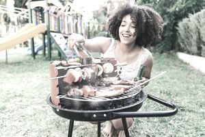 Smiling Woman Grilling at a BBQ