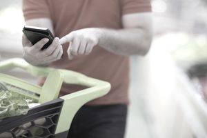 Man texting on smart phone while shopping for groceries