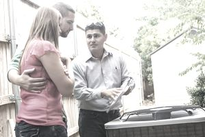 Air conditioner repairman explaining cost of repairs to homeowners.