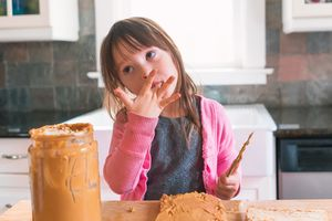 Young girl making peanut butter sandwich