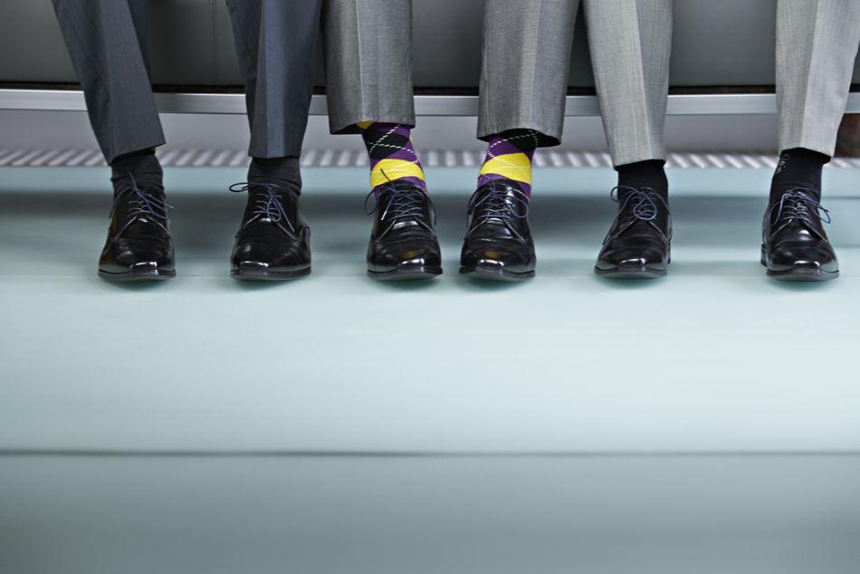 Business men's feet, one wearing crazy socks.