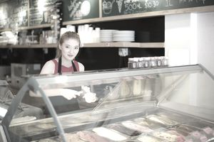 Young woman working in ice cream shop.