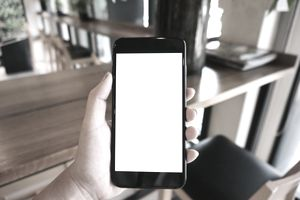 Cropped Hand Of Woman Holding Mobile Phone In Cafe