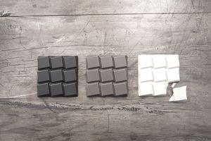 Dark, milk, and white chocolate bars lie waiting for consumption.
