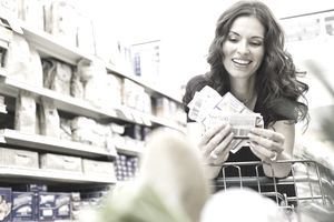 Woman shopping with coupons in grocery store