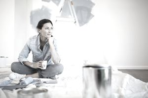Woman relaxing with coffee among painting supplies